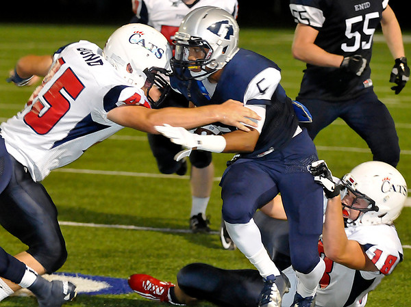 Enid's Johnny Lawrence struggles for yardage as Ponca City defenders, Cole Nimmo and John Bond combine to bring him down Friday at D. Bruce Selby Stadium. (Staff Photo by BILLY HEFTON)