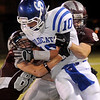 Garber defenders tackle Covington-Douglas's Quenten Thayer after a short gain Thursday. The Garber Wolverines led the Covington-Douglas Wildcats 20-14 at the half. (Staff Photo by BONNIE VCULEK)