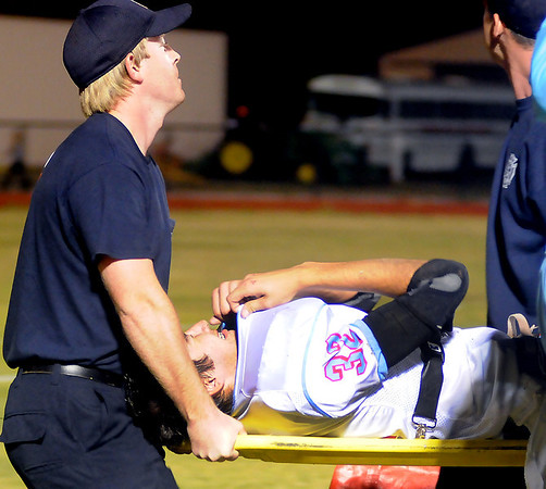 Enid firefighters carry Okeene's Hunter Miles from the field after Miles was injured during the Okeene vs OBA game Friday at Commitment Field. Miles underwent surgery to repair his leg Saturday. (Staff Photo by BONNIE VCULEK)
