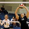 Guymon's Megan Rogers (right) sets the ball for a Lady Tiger teammate as OBA's Ashley Atwood (left) gets ready for a return volley Tuesday during the OSSAA 5A regional volleyball tournament finals at Oklahoma Bible Academy. OBA defeated Guymon 25-11, 25-17 and 25-15 to win the title. (Staff Photo by BONNIE VCULEK)