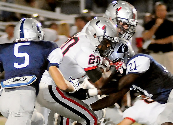 Enid's Jesse Cartwright (5) and Marshawn Mills (21) tackle Tulsa Union's Derek Finch during the Redskins' 52-0 win over the Plainsmen at D. Bruce Selby Stadium Friday, Oct. 11, 2013. (Staff Photo by BONNIE VCULEK)