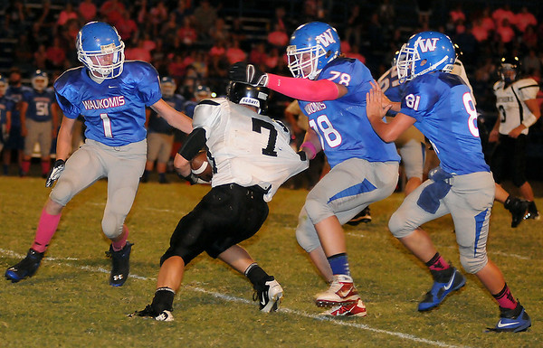 Waukomis Chiefs (from left) Dustin Breeze, Jared Lawson and Aaron Harrington zero in on Pond Creek-Hunter's Trenton Grimes, but the elusive Grimes avoided the tackles and scored for the Panters Thursday, Oct. 3, 2013. (Staff Photo by BONNIE VCULEK)