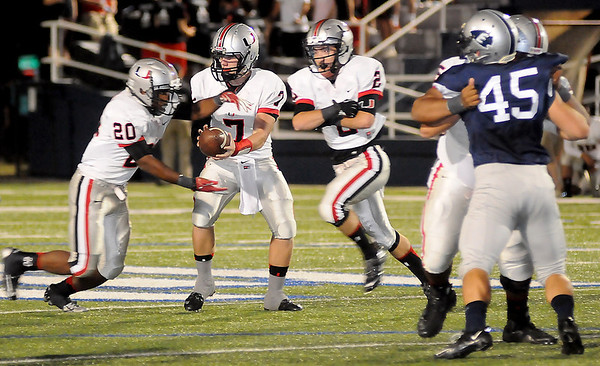Tulsa Union's Mason Farquhar (7) hands the ball off to Shayne Wess (20) against Enid during the Redskins' 52-0 win over the Plainsmen at D. Bruce Selby Stadium Friday, Oct. 11, 2013. (Staff Photo by BONNIE VCULEK)