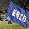 An Enid High student carries the Enid flag down the field at D. Bruce Selby Stadium after a Plainsmen score.