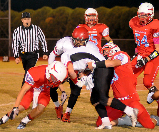 Chisholm's Bailey Cross and Bryce Stewart tackle a Pawnee Black Bear ball carrier Friday, Oct. 25, 2013. (Staff Photo by BONNIE VCULEK)