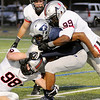 Tulsa Union's Chance Wenglewski (98) and JoJo Ogundare (99) tackle Enid's Freddie Lawrence for a loss during the Redskins' 52-0 victory over the Plainsmen at D. Bruce Selby Stadium Friday, Oct. 11, 2013. (Staff Photo by BONNIE VCULEK)