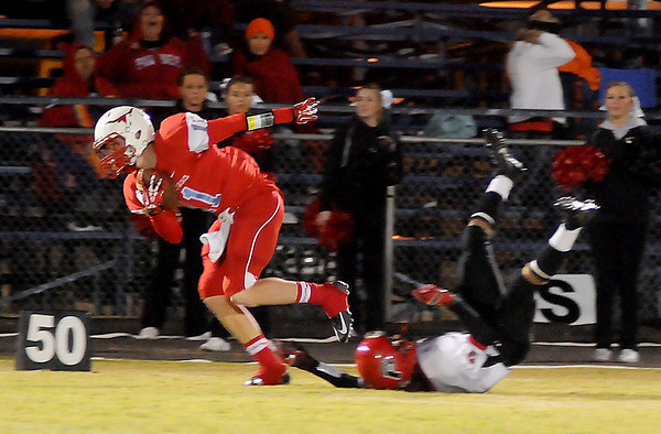 Chisholm's Austin Swann catches a deflected pass off the helmet of a Pawnee Black Bear defensive player and scampers into the end zone for a Longhorn touchdown Friday, Oct. 25, 2013. (Staff Photo by BONNIE VCULEK)