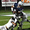 Enid's Will Phillips is brought down by Midwest City's T'Aces Vick and Kyle Lindsay Friday October 28, 2016 at D. Bruce Selby Stadium. (Billy Hefton / Enid News & Eagle)