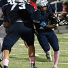 Enid's Khalid Lee runs off the block of Austin Whitehead against Lawton Friday October 13, 2017 at D. Bruce Selby Stadium in Enid. (Billy Hefton / Enid News & Eagle)