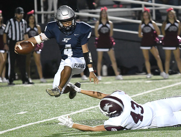 Enid's Sebastian Dimaricut leaps over the arms of Jenks's Ian Flute during a kickoff return Friday, October 4, 2019 at D. Bruce Selby Stadium. (Billy Hefton / Enid News & Eagle)