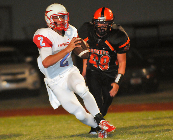 Chisholm's Taggart Brown runs away from Fairview's Spencer Eldred Friday at Eubanks Field in Fairview. (Staff Photo by BILLY HEFTON)