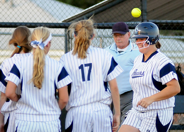 Enid's Ally Lewis celebrates at home plate with her teammates after hitting a monstrous home run over the left field fence, giving the Pacers' a 1-0 lead over the Stillwater Lady Pioneers in the bottom of the first inning at Pacer Field Monday, Sept. 23, 2013. (Staff Photo by BONNIE VCULEK)