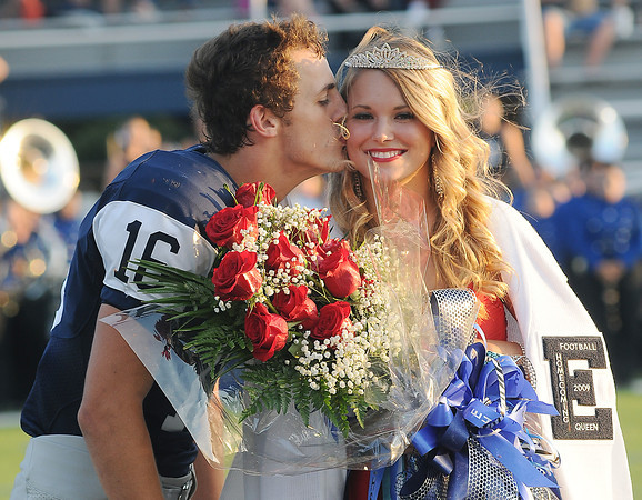 Enid High School Plainsmen homecoming football king, Aaron Beagle, gives homecoming queen, MacKenzie Moulton, a kiss on the cheek during pre-game festivities at D. Bruce Selby Stadium Friday, Sept. 27, 2013. (Staff Photo by BONNIE VCULEK)