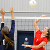 Chisholm's Shannon Grimes hits the ball over Enid's Grace Enmeier Monday at the Chisholm Middle School gym. (Staff Photo by BILLY HEFTON)