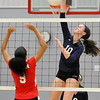 Enid's Chloe Cordell hits the ball over Chisholm's Riley Raynor Monday at the Chisholm Middle School gym. (Staff Photo by BILLY HEFTON)