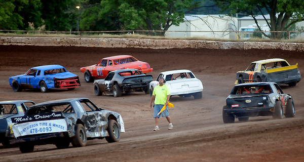 A racing official positions pure stocks for the start of the Enid Speedway race Saturday, Sept. 7, 2013. (Staff Photo by BONNIE VCULEK)