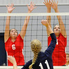 Chisholm's Elizabeth Bullard and Asheley Middleton reach to attempt a block of a shot by Enid's Shaelyn Vaughn Monday at the Chisholm Middle School gym. (Staff Photo by BILLY HEFTON)