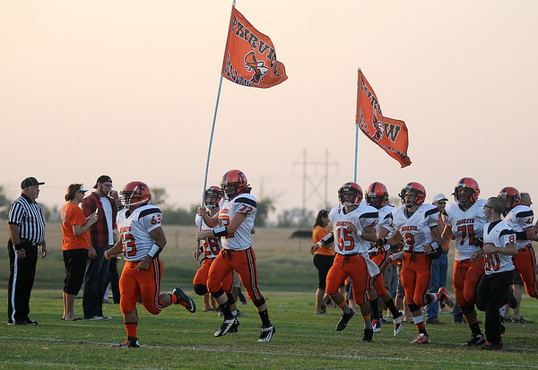 The Fairview Yellowjackets sprint onto the field as they open the 2013 football season against the Pioneer Mustangs at Pioneer High School. (Staff Photo by BONNIE VCULEK)