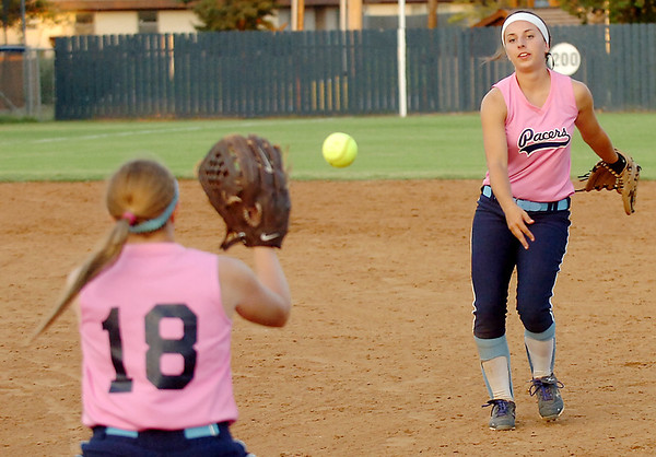 Abby Lee tosses the ball to Makaya Herst for an out against Owasso Tuesday at Pacer Field. (Staff Photo by BILLY HEFTON)