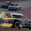 Tyler Pembrook breaks away around turn 4, as he battles his way through the 16 pure stocks, taking the checkered flag in the first race at the Enid Speedway Saturday, Sept. 7, 2013. (Staff Photo by BONNIE VCULEK)