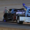 Dewayne Grimm's pure stock is towed to the pits by Stanley's Wrecker Service and racing officials after it caught fire on the back straight away near turn three at the Enid Speedway Saturday, Sept. 7, 2013. Grimm was not injured. (Staff Photo by BONNIE VCULEK)