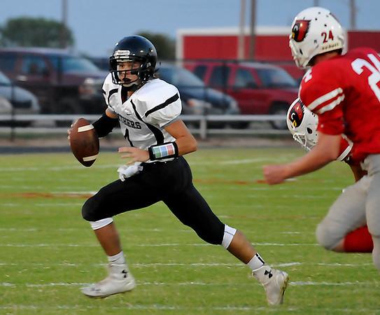 Pond Creek-Hunter quarterback, Cole Jones, scrambles away from Medford defenders Thursday September 3, 2015 at Medford High School. (Staff Photo by BILLY HEFTON)