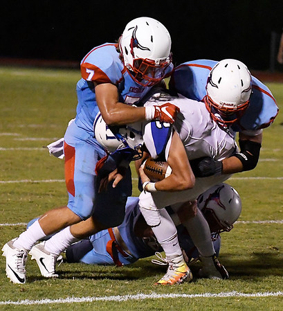 Chisholm's Mason McKee, Beaux Biggers and Brice Chance combine to bring down Hennessey's Levi Childs Friday September 30, 2016 at Chisholm High School. (Billy Hefton / Enid News & Eagle)