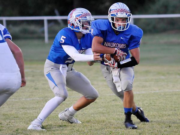 Waukomis' Lane Briggs takes the handoff from Hunter Lovell Thursday September 1, 2016 against Covington-Douglas at Waukomis HIgh School. (Billy Hefton / Enid News & Eagle)