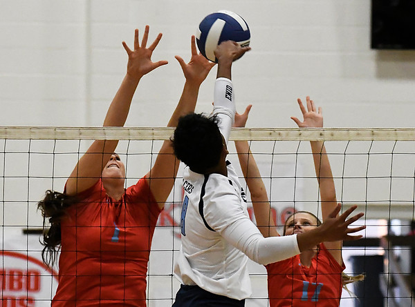 Chisholm's Cadee Fromm and Gabby Bartley go up to block the hit by Enid's D'Sani Levy Tuesday September 5, 2017 at the NOC Mabee Center. (Billy Hefton / Enid News & Eagle)