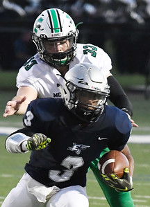 Enid's Jadon Dimarcut tries to get away from McGuinness's Brandon Jacobs Friday September 14, 2018 at D. Bruce Selby Stadium. (Billy Hefton / Enid News & Eagle)