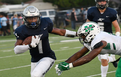 Enid's Will Phillips pushes away McGuinness's Brynden Walker Friday September 14, 2018 at D. Bruce Selby Stadium. (Billy Hefton / Enid News & Eagle)