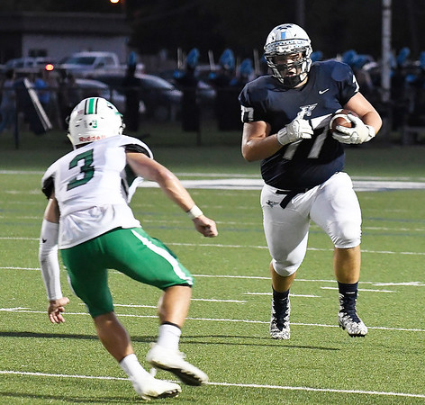 Enid's Kaleb Stanley carries the ball on a hook and ladder play against McGuinness's Aaron Beck Friday September 14, 2018 at D. Bruce Selby Stadium. (Billy Hefton / Enid News & Eagle)