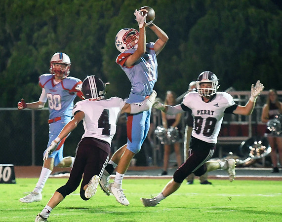 Chisholm's Leyton Parker intercepts a pass between Perry's Ethan Calhoon and Wyatt Boyd Friday, September 27, 2019 at Chisholm High School. (Billy Hefton / Enid News & Eagle)