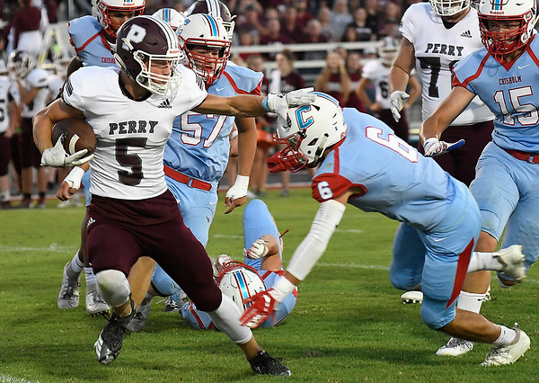 Perry's Kohl Witter tries to get around Chisholm's Jacob Cusick Friday, September 27, 2019 at Chisholm High School. (Billy Hefton / Enid News & Eagle)