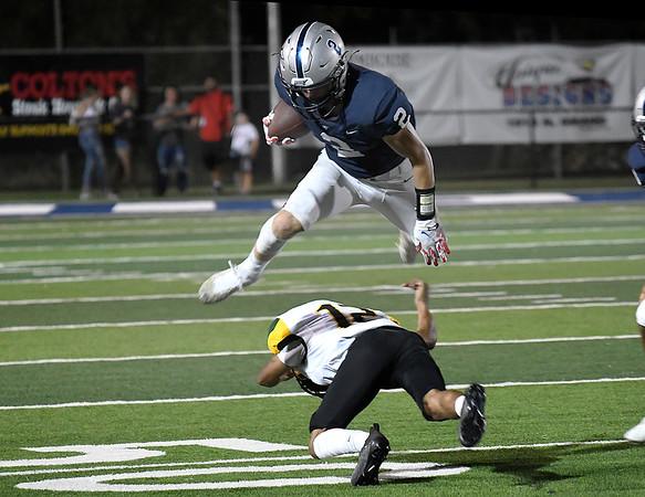 Enid's Seth Carlson leaps over MacArthur's A.J. Vaughn Friday, September 17, 2021 at D. Bruce Selby Stadium. (Billy Hefton / Enid News & Eagle)