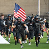 Pond Creek-Hunter's Cole Mitchell carries the American flag as the team runs onto the field Thursday, September 2, 2021 at Pond Creek-Hunter High School. (Billy Hefton / Enid News & Eagle)