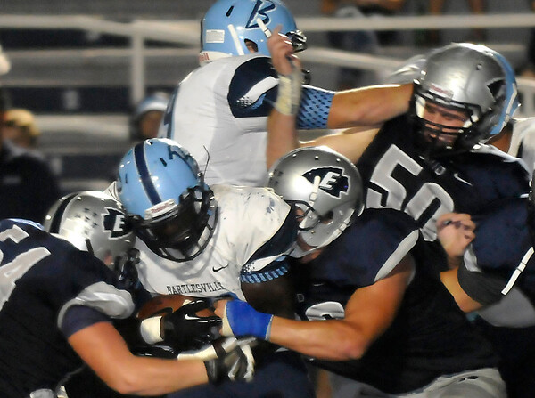 Enid's Jordan Wagner and Corey Ganz combine to bring down Bartlesville's Glenn Dickson Friday at D. Bruce Selby Stadium. (Staff Photo by BILLY HEFTON)
