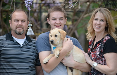 10-week-old yellow lab Enloe makes friends with his new family,  Jeff Hunt, 17-year-old Garrett Hunt and mom Traci Hunt at their Durham, Calif. home Tues. April 4, 2017. Enloe will be trained by Dina Zaphiris, founder & CEO, InSitu Foundation as a cancer finding dog. (Bill Husa -- Enterprise-Record)