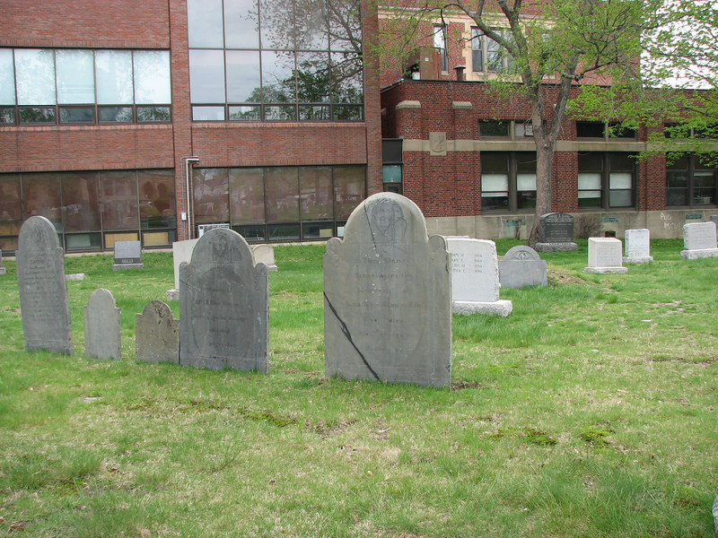 Brown's gravestone is in the center. Use this photo to help locate the grave. It is in the section of the cemetery closest to Common Street and farthest from Mount Auburn Street. The building in the rear is Watertown High School.