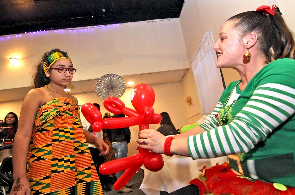 """. Lexie Sandoval 10, one of the African dancers from Lowell Community Charter Public School has a balloon santa made by \""""Miss Jackie\"""" Lee from The Party Fun, at the Enterprise Bank holiday party. SUN/ David H. Brow"""