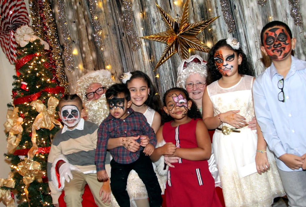 . Having their photo taken with Mr&Mrs Claus(played by John Moynihan and Faith Walsh), are kids of Enterprise employee\'s and friends L-R, Antonio Cortes 5, Isaac Rosario 18 months, Jelexa Cortes 10, Isabella Rosario 4, Jalexa Cortes 9, and Edarlin Medina 11, all at the annual Enterprise Bank International Holiday Party. SUN/ David H. Brow