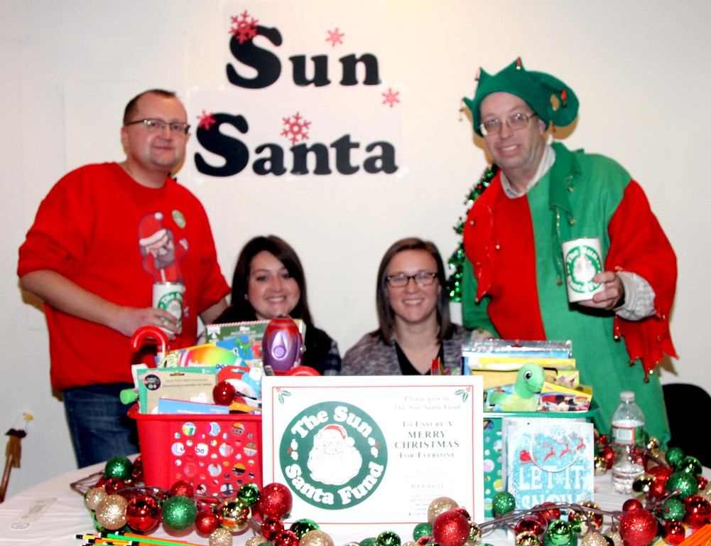 . Collecting money for the Sun Santa Fund at the 4th annual Enterprise Bank International Holiday Celebration is L-R, Stephen Morrison (volunteer/not employee), Jackie Silva, Shelby Descoteaux and Mark Watson, all employee\'s. SUN/ David H. Brow