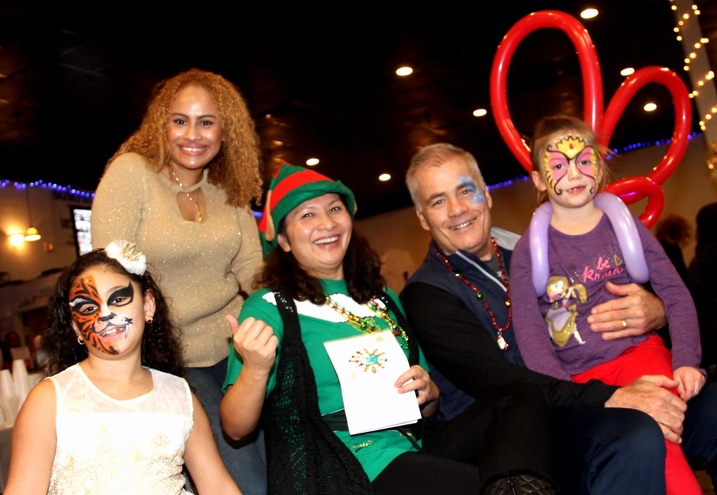. Having a fun time at the 4th annual Enterprise Bank International Holiday Celebration is L-R, Jalexa Cortes 9, her mom Jennifer De Los Santos (standing), Sophy Theam, Jack Clancy and his grandaughter Ellie Petro Roy 6. SUN/ David H. Brow