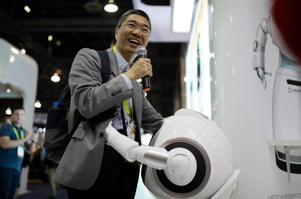 . Jun Wu gets a hug from the Cruzr cloud-based service robot at the Ubtech booth during CES International, Saturday, Jan. 7, 2017, in Las Vegas. (AP Photo/John Locher)