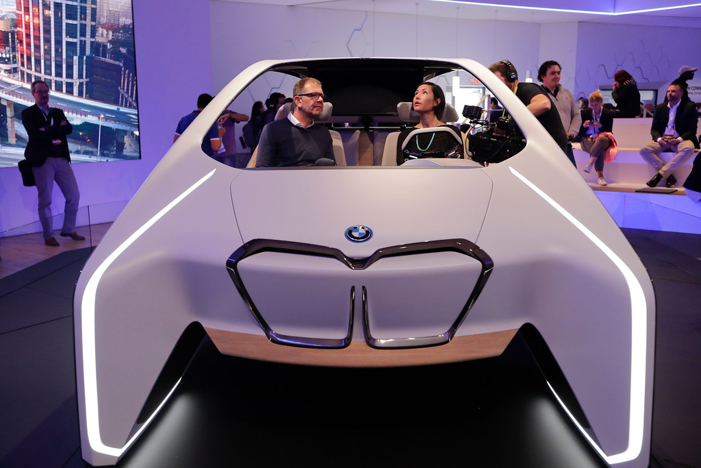 . Holger Hampf, BMW\'s head of user experience, left, and a reporter sit in the BMW i Inside Future concept, at CES International Thursday, Jan. 5, 2017, in Las Vegas. (AP Photo/Jae C. Hong)