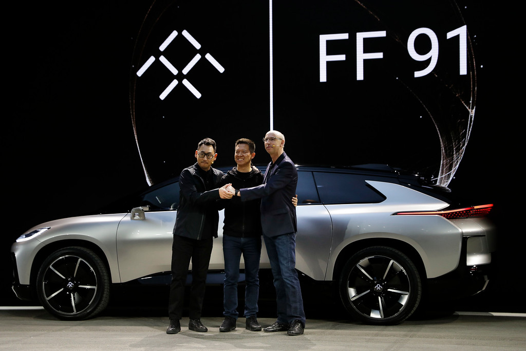 . LeEco CEO YT Jia, center, poses with Nick Sampson, Faraday Future\'s senior vice president of product research & development, right, and Richard Kim, vice president of design, after unveiling the FF91 electric car at CES International Tuesday, Jan. 3, 2017, in Las Vegas. (AP Photo/Jae C. Hong)