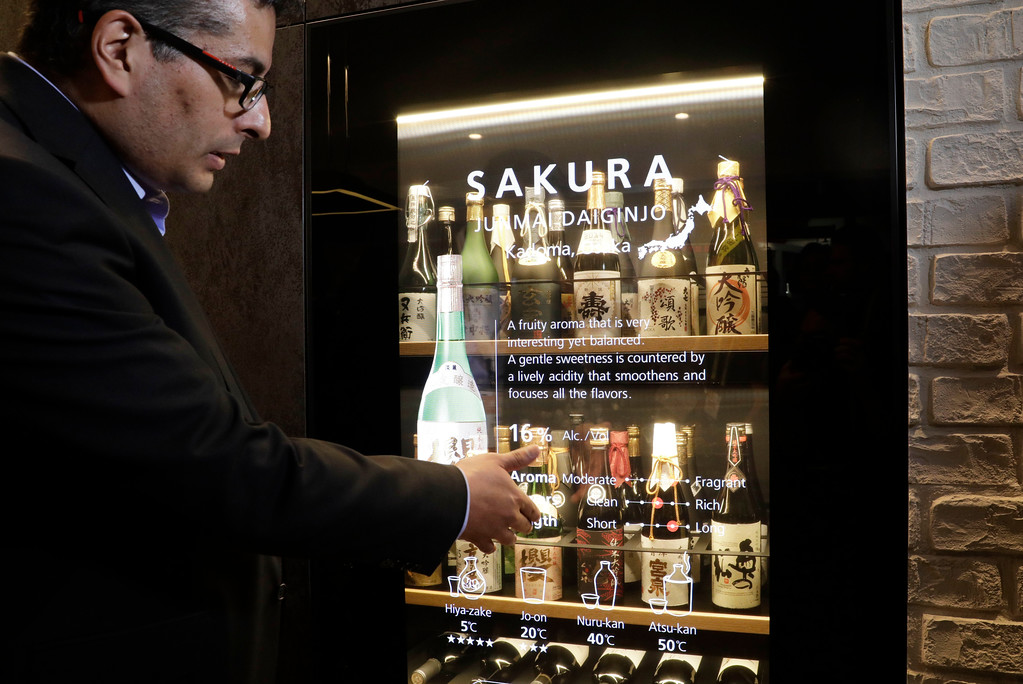. Mario Gonzalez talks about the interactive Wine and Sake Cellar at the Panasonic booth during CES International, Thursday, Jan. 5, 2017, in Las Vegas. (AP Photo/John Locher)