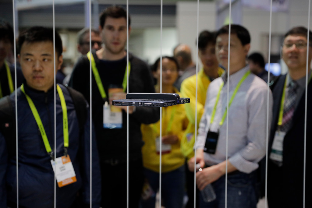 . Show attendees watch the flying demonstration of a Hover Camera drone, also known as a selfie drone, at CES International on Thursday, Jan. 5, 2017, in Las Vegas. (AP Photo/Jae C. Hong)
