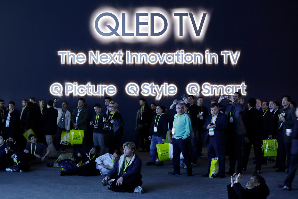 . Attendees watch a presentation on a screen about the QLED TV at the Samsung booth during CES International, Friday, Jan. 6, 2017, in Las Vegas. (AP Photo/John Locher)