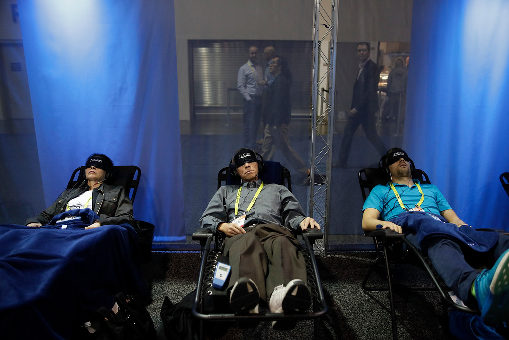 . Show attendees try out NuCalm\'s products designed to lower stress and improve sleep quality at CES International Friday, Jan. 6, 2017, in Las Vegas. (AP Photo/Jae C. Hong)
